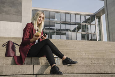 Blond businesswoman having a lunch outside and using smartphone - AHSF01370