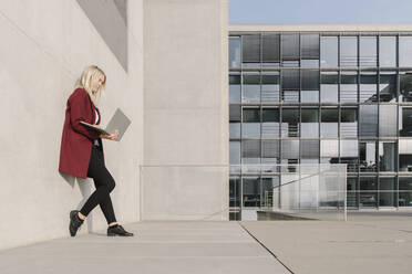 Blond businesswoman using laptop and leaning on a wall - AHSF01373