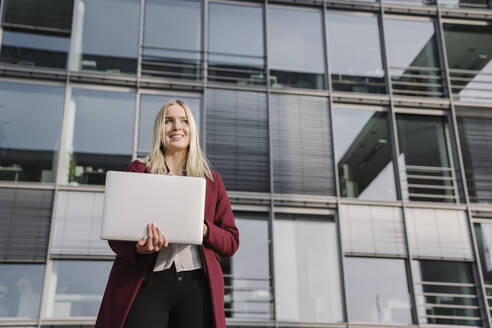Blond businesswoman with laptop in the background of modern office building - AHSF01376