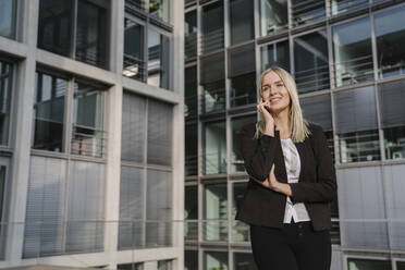 Blond businesswoman using smartphone in the background modern building - AHSF01379