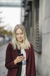 Blond businesswoman using smartphone in the city, looking down - AHSF01391