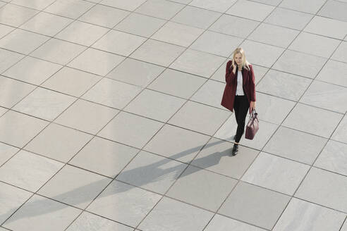 View from above of blond businesswoman using smartphone, walking on concrete ground - AHSF01394