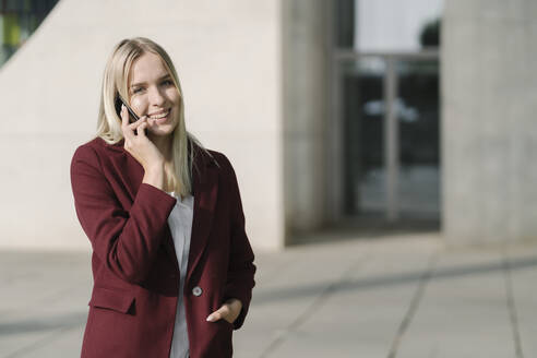 Blond businesswoman using smartphone, looking at camera - AHSF01397