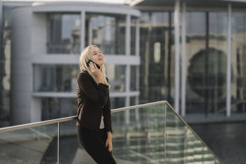 Blond businesswoman using smartphone in the background modern building - AHSF01406