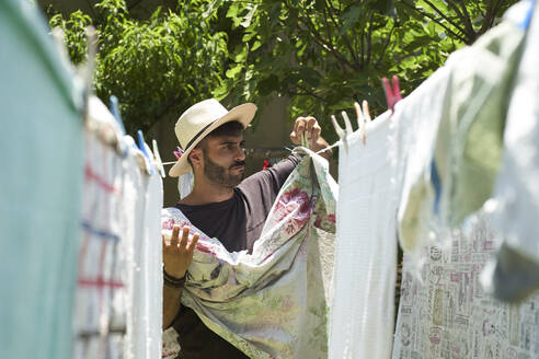 Man hanging up laundry outdoors - VEGF00902