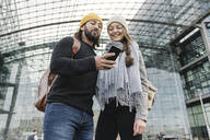 Happy young couple using a smartphone at the central station, Berlin, Germany - AHSF01416