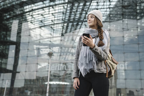 Young woman with smartphone waiting at the central station, Berlin, Germany - AHSF01419