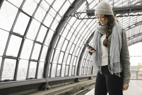 Happy young woman using smartphone at the station platform, Berlin, Germany - AHSF01425