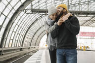 Happy young couple at the station platform, Berlin, Germany - AHSF01428