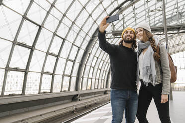 Happy young couple taking a selfie at the station platform, Berlin, Germany - AHSF01437