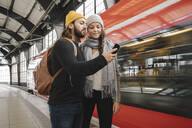 Young couple using smartphone at the station platform as the train comes in, Berlin, Germany - AHSF01452
