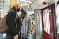 Young couple kissing on a subway - AHSF01458