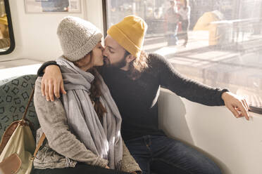 Young couple kissing on a subway - AHSF01461