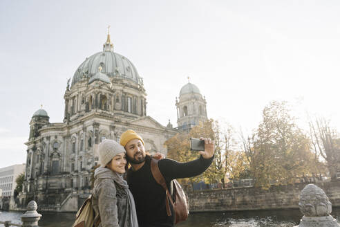 Young couple taking a selfie with Berlin Cathedral in background, Berlin, Germany - AHSF01470