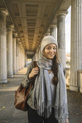Portrait of smiling young woman in arcade in the city, Berlin, Germany - AHSF01479