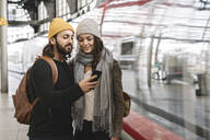 Young couple using smartphone at the station platform as the train comes in, Berlin, Germany - AHSF01500