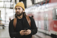 Young man with smartphone at the station platform, Berlin, Germany - AHSF01503