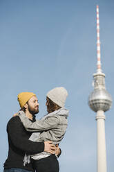 Young couple embracing with television tower in background, Berlin, Germany - AHSF01512