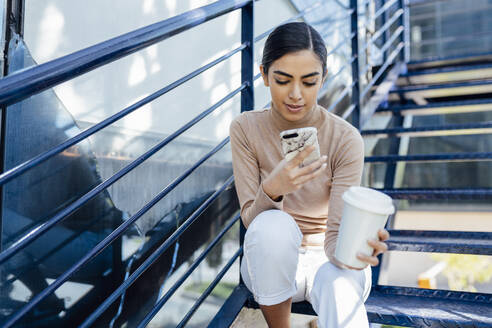 Young woman with takeaway drink sitting on exterior stairs using smartphone - JSMF01369