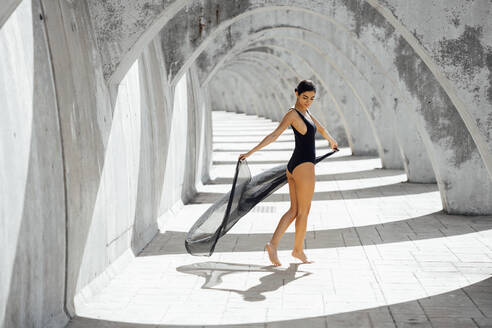 Young woman wearing black swimsuit dancing in an archway - JSMF01396