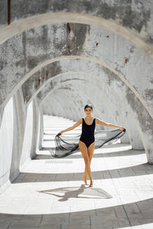 Young woman wearing black swimsuit dancing in an archway - JSMF01399