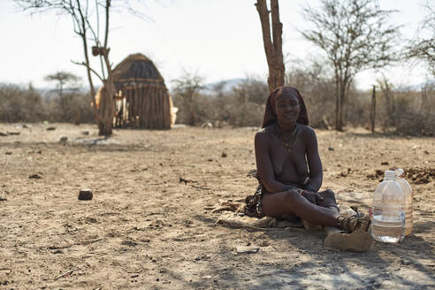 Himba woman sitting on sandy soilin her village, Opuwo, Namibia - VEGF00933