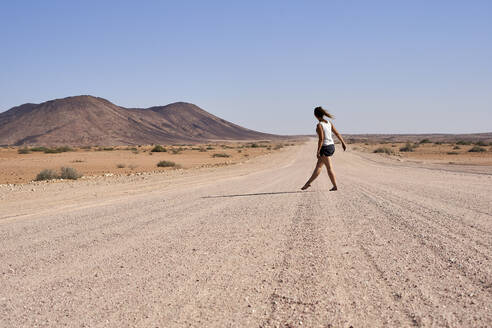 Woman walking in the middle of a dirt road, Damaraland, Namibia - VEGF00939