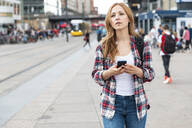 Woman with smartphone in the city, Berlin, Germany - WPEF02299