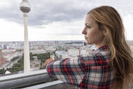 Woman looking at view of the city with television tower, Berlin, Germany - WPEF02302
