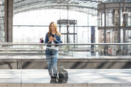 Woman using smartphone at the train station, Berlin, Germany - WPEF02317