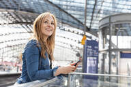 Smiling woman with smartphone  at the train station, Berlin, Germany - WPEF02320