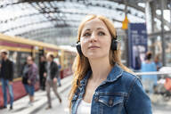 Portrait of woman listening to music with headphones at the station, Berlin, Germany - WPEF02323