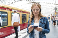 Smiling woman with smartphone and headphones on the station platform, Berlin, Germany - WPEF02326