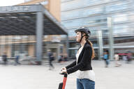 Woman riding e-scooter in the city, Berlin, Germany, Berlin, Germany - WPEF02338