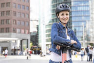 Portrait of smiling woman with e-scooter in the city, Berlin, Germany - WPEF02350