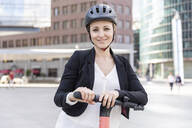 Portrait of smiling woman with e-scooter in the city, Berlin, Germany - WPEF02359