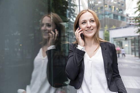 Smiling businesswoman on the phone in the city - WPEF02362