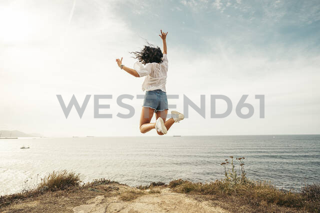 Rear view of yung woman jumping on viewpoint, Getxo, Spain - MTBF00229 - Mikel Taboada/Westend61