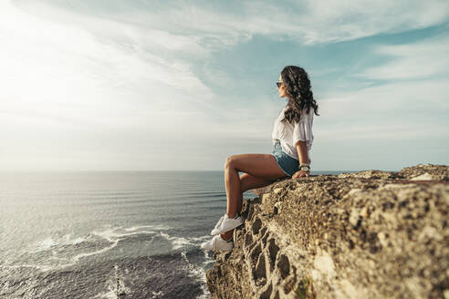 Young woman sitting on viewpoint and looking at distance, Getxo, Spain - MTBF00235
