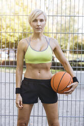 Blonde woman with basketball in Cologne, Germany - MADF01406