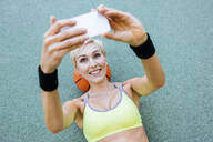Blonde woman lying on basketball and taking a selfie - MADF01409