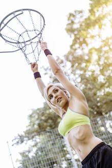Blonde woman playing basketball, hanging on hoop - MADF01418