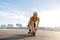 Blonde woman jogging, tying shoes - MADF01421