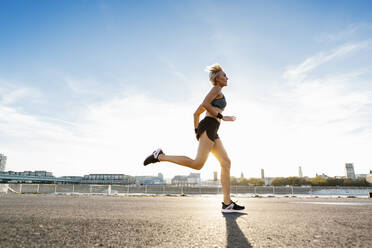 Blonde woman jogging in Cologne, Germany - MADF01424