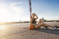 Blonde woman sitting with basketball on playing field in Cologne, Germany - MADF01430