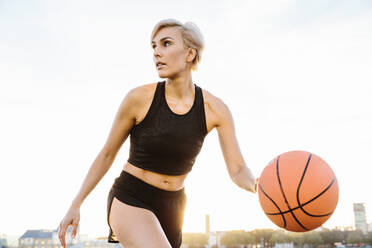 Blonde woman playing basketball, looking sideways - MADF01433