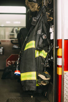 USA, New York, Fire protection suit hanging inside fire engine - CJMF00182