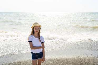 Girl with straw hat standing on the beach, Tuscany, Italy - OJF00359