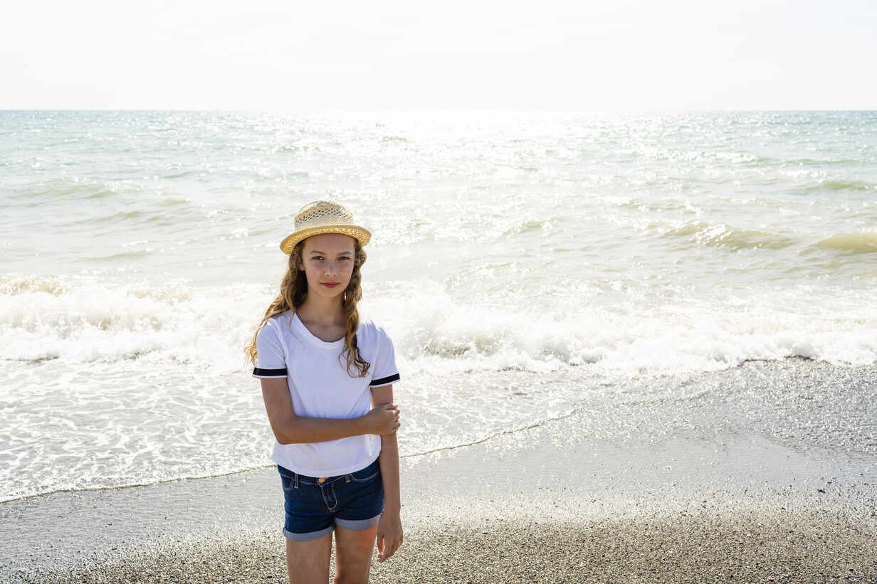 Girl with straw hat standing on the beach, Tuscany, Italy - OJF00359 - Julia Otto/Westend61