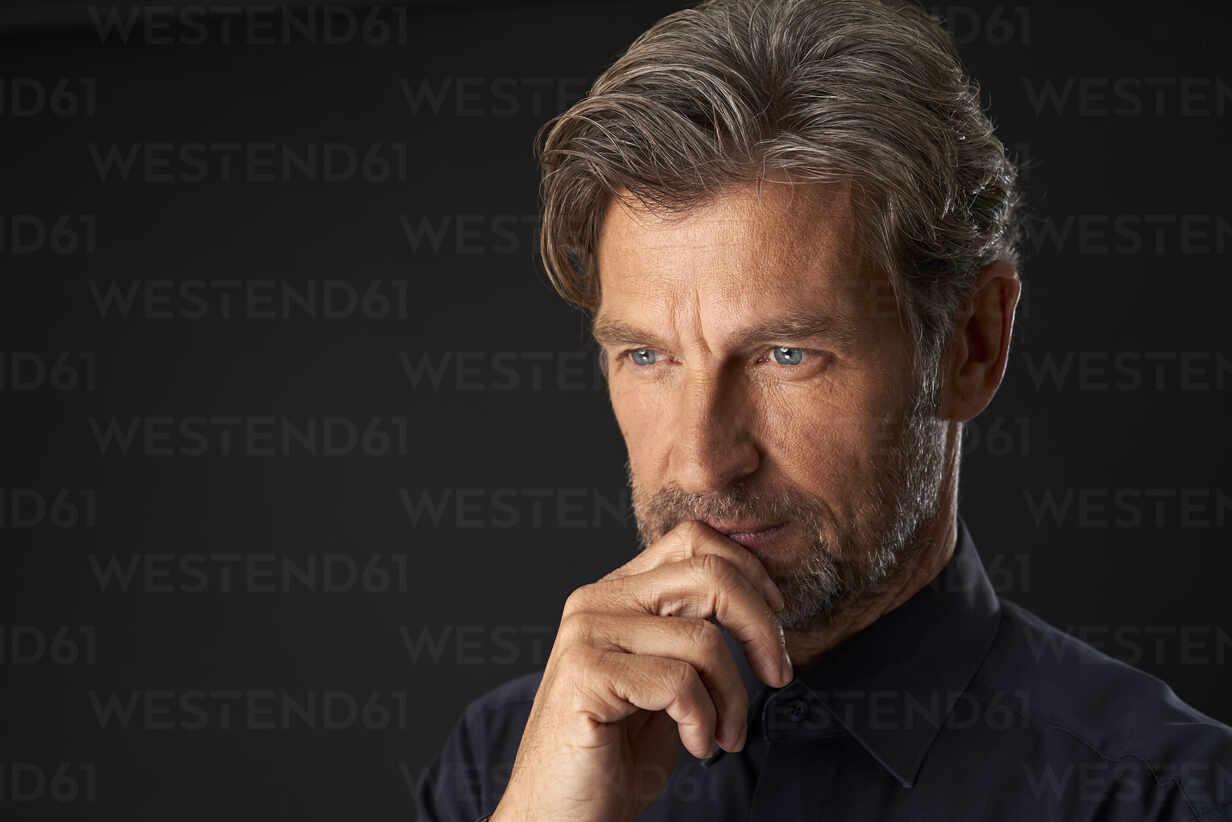 Portrait of pensive mature businessman against dark background - PHDF00005 - Isabella Bellnini/Westend61